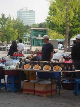 A vendor outside the stadium selling chicken and beer all bagged up and ready to go.