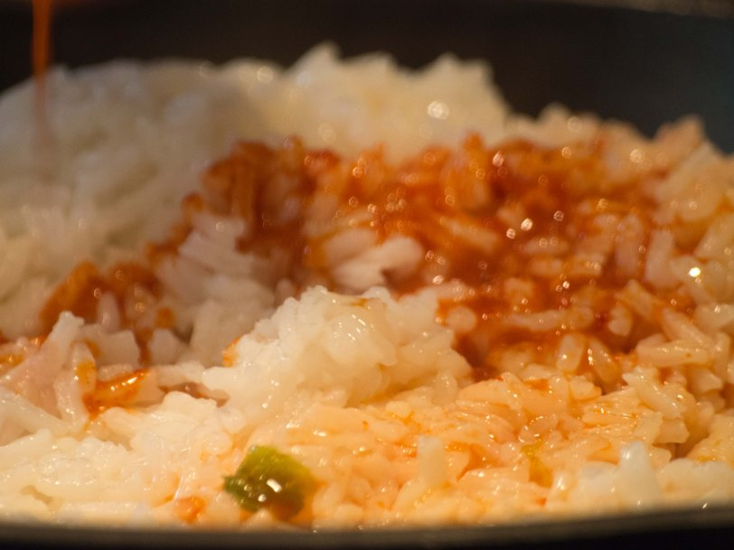 Pouring Kimchi Juice into Rice for Kimchi Fried Rice